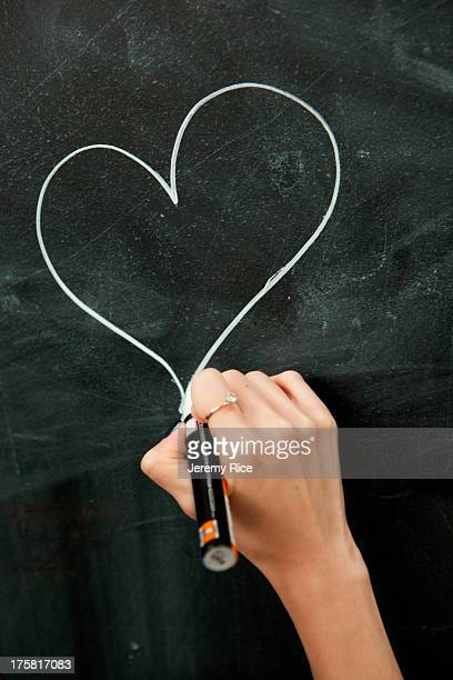 Young woman drawing heart on blackboard