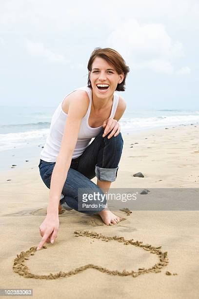 Young woman drawing heart shape symbol in sand