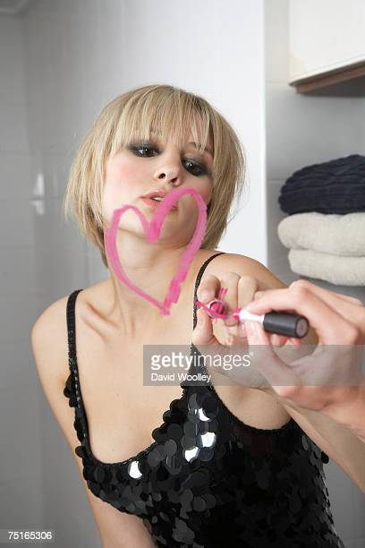 young woman drawing heart shape with lipstick on mirror - dessin erotique photos et images de collection
