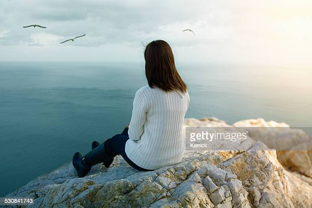 young woman dreaming on cliff