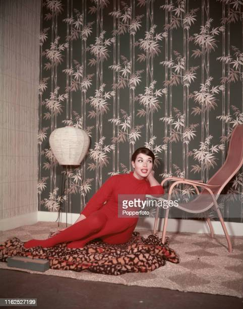 A young woman dressed all in red seated on an animal pattern throw beside a wooden lounger chair in the living room of a house in England in June...