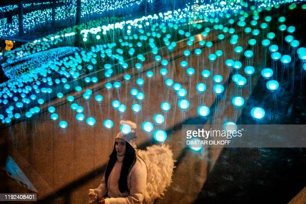 A young woman dressed as an angel pictured through a glass walks at the Zaryadye Park illuminated with Christmas lights in Moscow on January 7 2020...