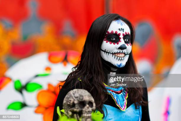 A young woman dressed as La Catrina a Mexican pop culture icon who represents Death smiles during the Day of the Dead festival on October 28 2016 in...