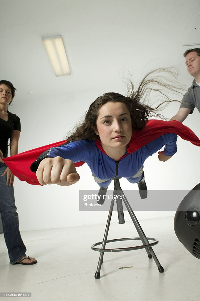 Young woman dressed as superwoman, in studio : Stock Photo