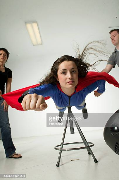 Young woman dressed as superwoman, in studio