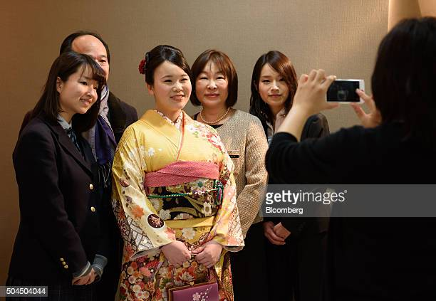 A young woman dressed in a furisodestyle kimono for her Coming of Age Day ceremony poses for a photograph with her family at a photo studio in...