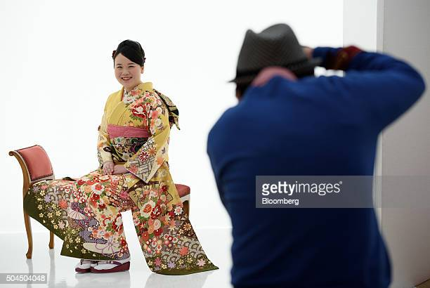 A young woman dressed in a furisodestyle kimono for her Coming of Age Day ceremony poses for a portrait at a photo studio in Kawasaki City Kanagawa...