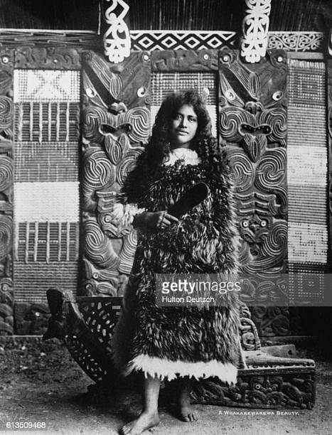 A young woman dressed in fur stands in front of a carved wooden backdrop