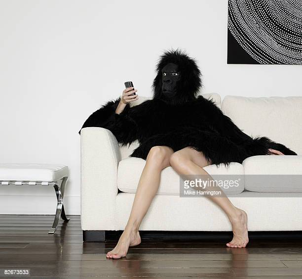 young woman dressed in gorilla suit using mobile  - monkey suit stock pictures, royalty-free photos & images