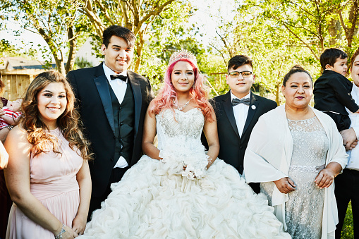 Young woman dressed in quinceanera gown standing in backyard surrounded by family - gettyimageskorea