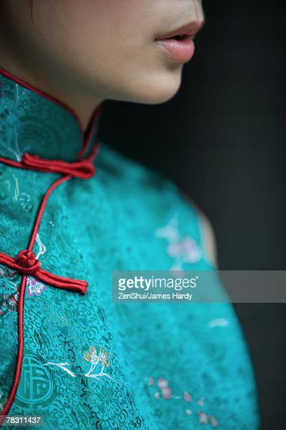 Young woman dressed in traditional Chinese clothing, cropped view of lower face and bust