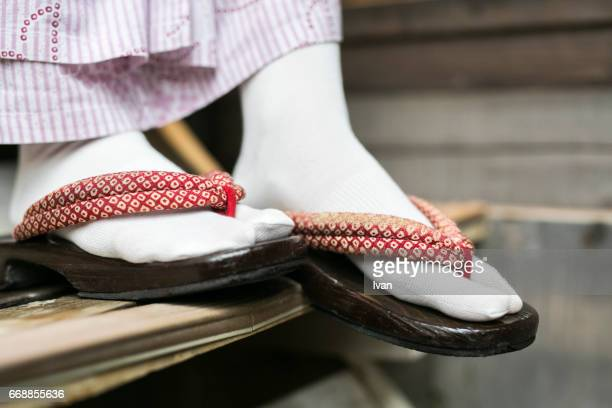 Young Woman Dresses Traditional Japanese Slippers, Geta Sandals, and goes down the stairs