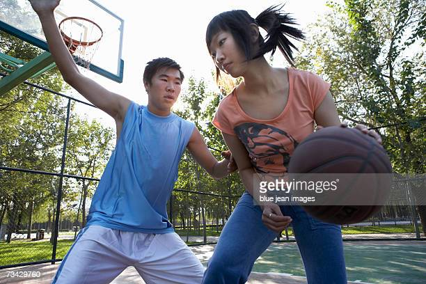 A young woman dribbles the basketball on an outdoor basketball court, a young man plays defense.