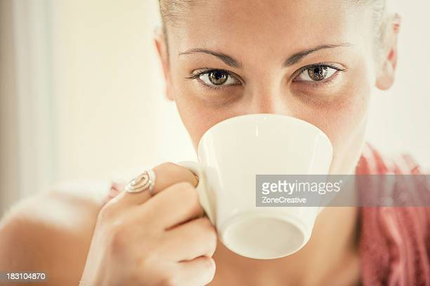 Young woman drink a cup of coffee at italian café