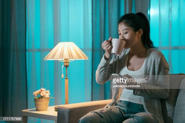 若い女性は携帯電話を使ってコーヒーを飲む - 真夜中 ストックフォトと画像