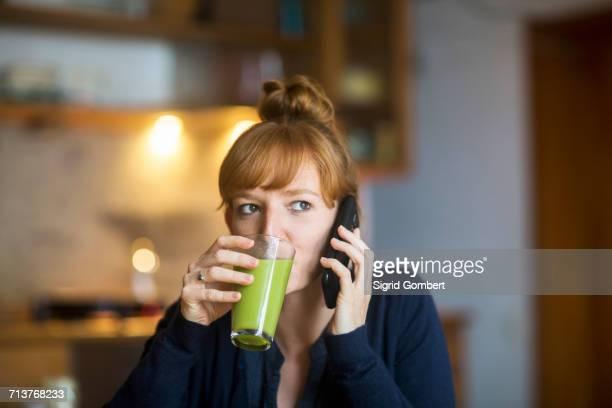 young woman drink smoothie, using smartphone - sigrid gombert - fotografias e filmes do acervo