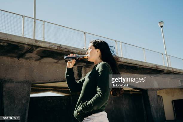 Young woman drinking a bottle of cold drink