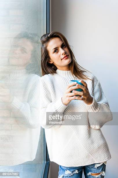 young woman drinking a coffee at a window - hot spanish women stock pictures, royalty-free photos & images