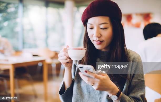 Young woman drinking a cup of coffee and text messaging on mobile phone