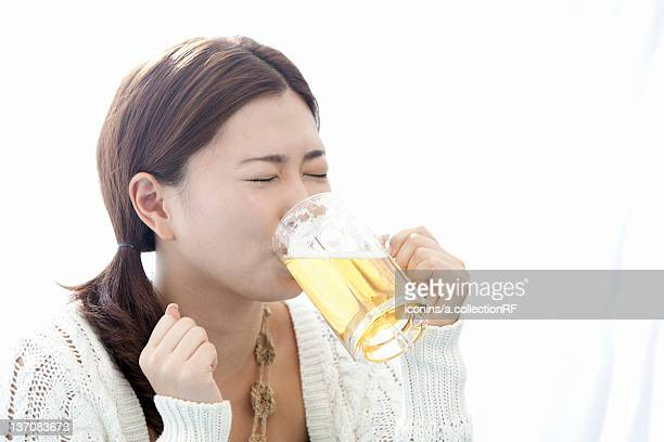 Young woman drinking a glass of beer, Tokyo Prefecture, Honshu, Japan