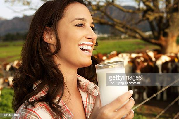 Young woman drinking a glass of milk on a dairy farm