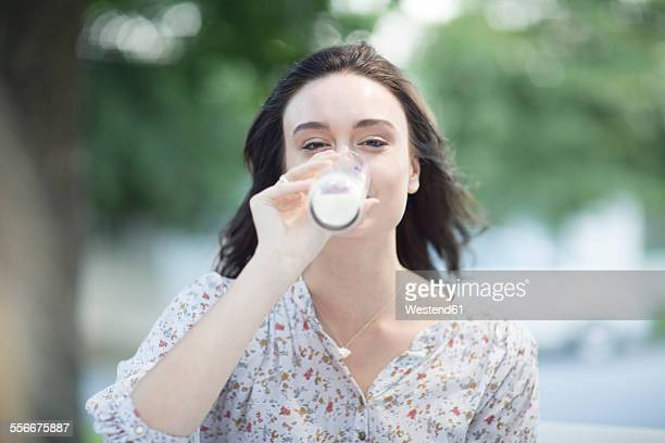 Young woman drinking a glass of milk outdoors