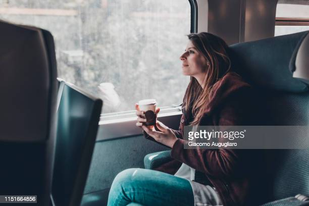 young woman drinking a hot drink on tgv train, paris, france, europe - hot women pics ストックフォトと画像