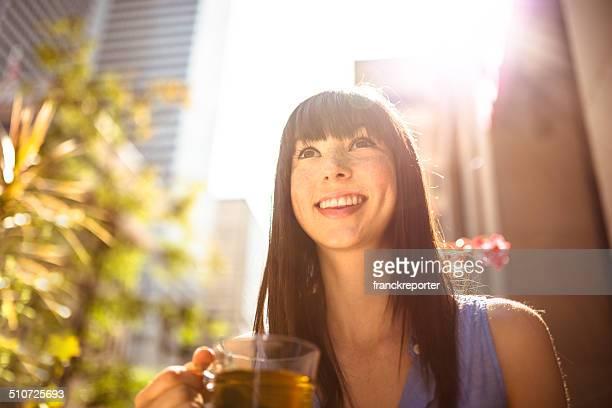 若い女性のティーを飲みながら、街