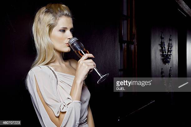 Young woman drinking alone in club
