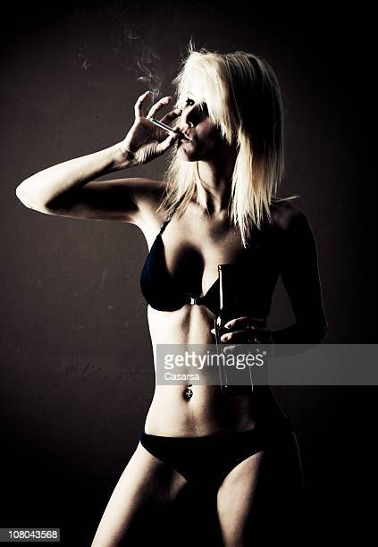 Young woman drinking and smoking