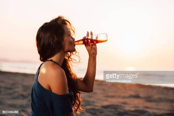 Junge Frau am Strand trinken