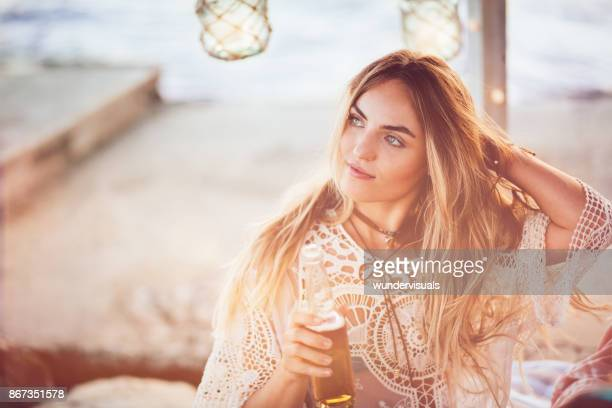 Young woman drinking beer at beach bar on summer holidays
