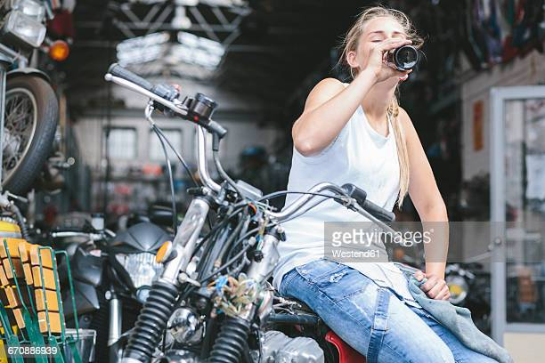 Young woman drinking beer from bottle on motorbike
