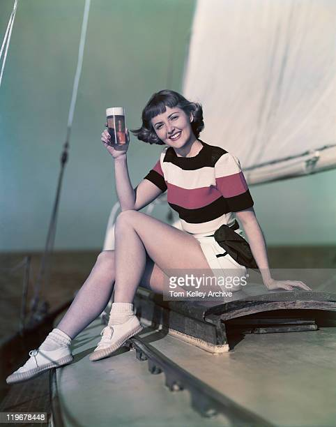 Young woman drinking beer in sailing boat, smiling, portrait