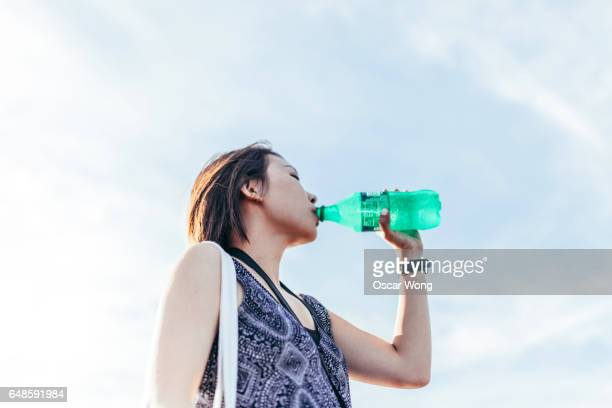 young woman drinking bootle water - soda stock pictures, royalty-free photos & images