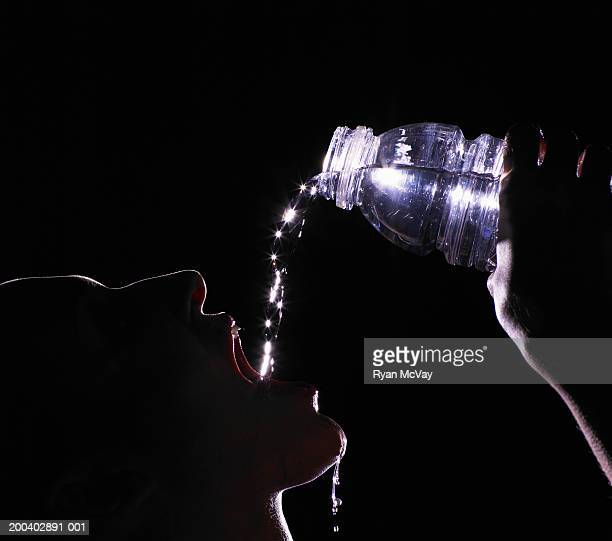 Young woman drinking bottled water, head back, profile