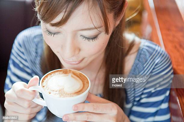 Young woman drinking cappccino, high angle view