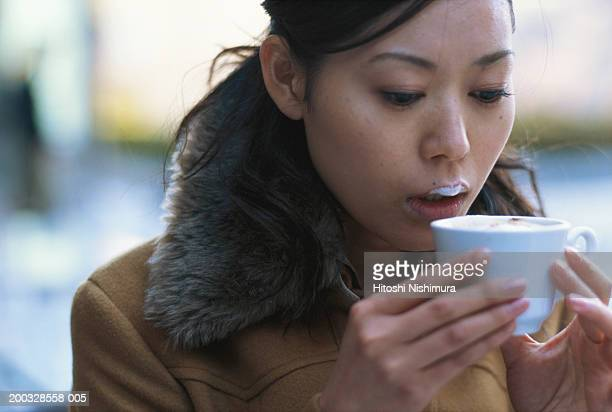 Young woman drinking cappuccino, close-up