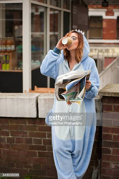 Young woman drinking cappuccino in a onesie
