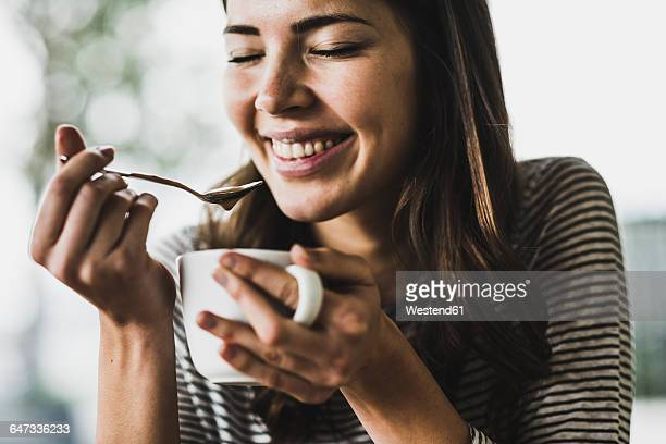 young woman drinking cappuccino, spooning milk froth - vergnügen stock-fotos und bilder