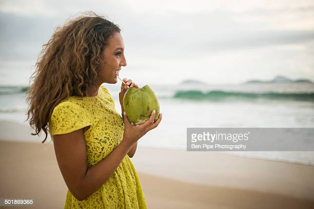 young woman drinking coconut milk on ipanema beach, rio de janeiro, brazil - tropical fruit stock pictures, royalty-free photos & images