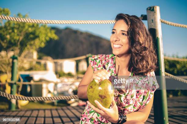 young woman drinking coconut water at rio de janeiro - coconut water stock pictures, royalty-free photos & images