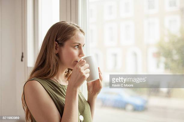 Young woman drinking coffee and gazing through sitting room window