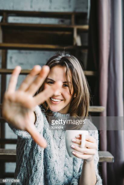 Young woman drinking coffee and hiding from the camera
