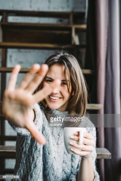 Jonge vrouw drinken koffie en het verbergen van de camera