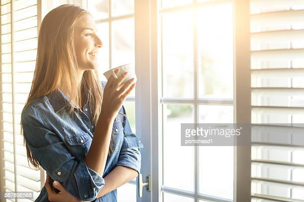 young woman drinking coffee and looking through window - zonnestraal stockfoto's en -beelden