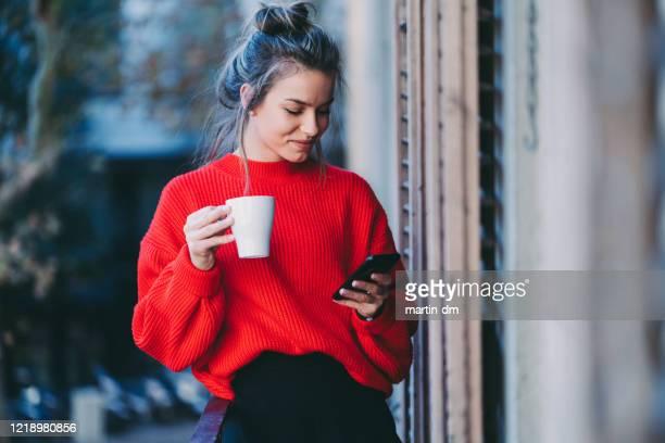 joven bebiendo café y enviando mensajes de texto - mujeres jóvenes fotografías e imágenes de stock