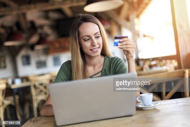 Young woman drinking coffee and using credit card in cafeteria