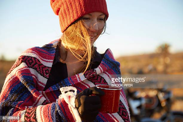 Young woman drinking coffee at campsite