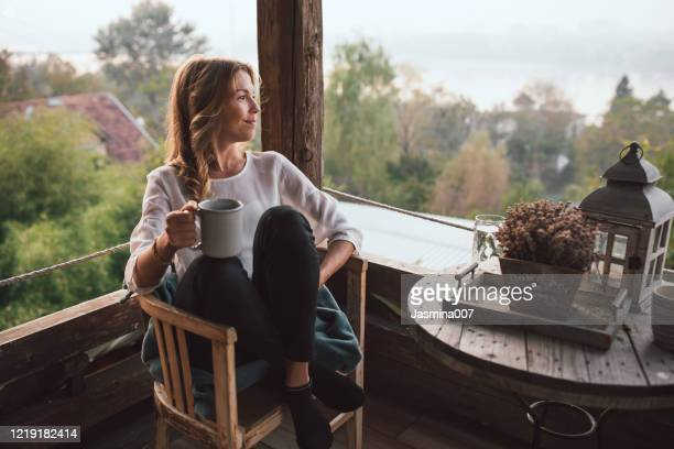 young woman drinking coffee at home - moment of silence stock pictures, royalty-free photos & images